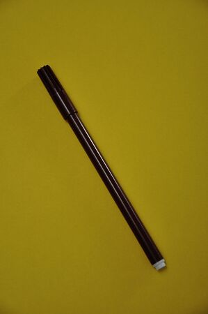 A brown pen isolated on a yellow background