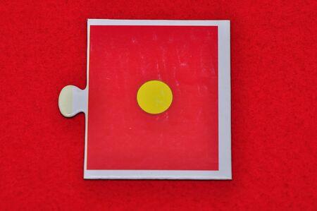A jigsaw piece with one dot