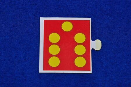 A jigsaw piece with seven dots Stock Photo