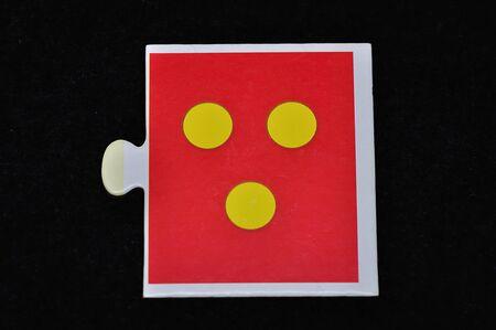 A jigsaw piece with three dots