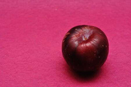 A ripe plum on a pink background Stock Photo