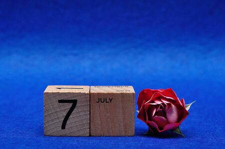 7 July on wooden blocks with a red rose on a blue background Stock Photo