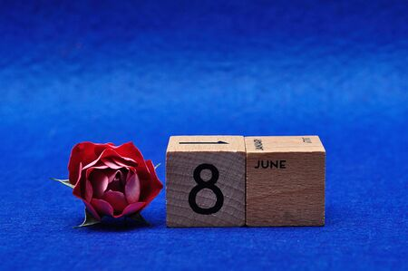 8 June on wooden blocks with a red rose on a blue background