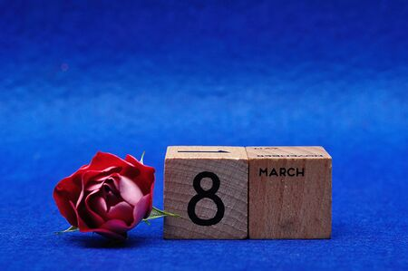 8 March on wooden blocks with a red rose on a blue background