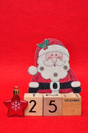 25 December on wooden blocks with a red star and a christmas father on a red background Stock Photo