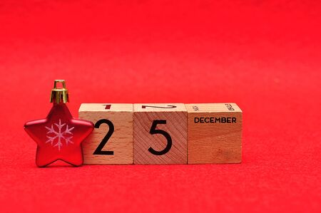 25 December on wooden blocks with a red star on a red background