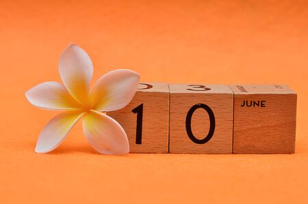 10 June on wooden blocks with a Frangipani flower on an orange background Stock Photo