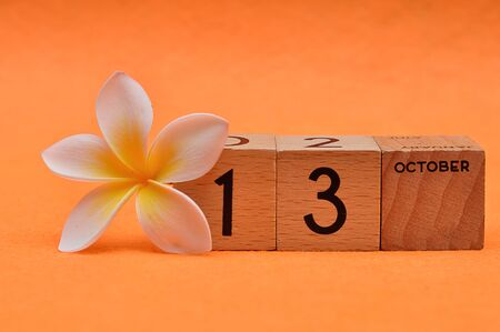 13 October on wooden blocks with a Frangipani flower on an orange background