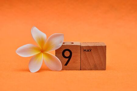 9 May on wooden blocks with a Frangipani flower on an orange background