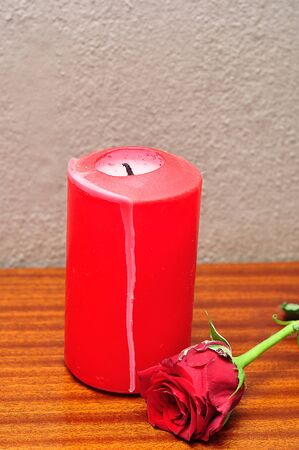 A red candle with a red rose