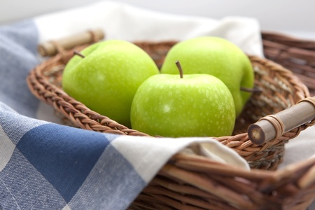 willow fruit basket: Green apples in the brown wicker basket with a blue gingham cloth