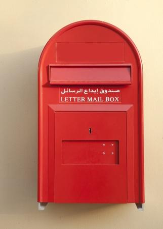 arabische letters: Een rode brievenbus met Engels en Arabisch letters Stockfoto
