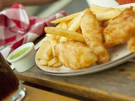 fish and chips: Pescado y patatas fritas. Merienda tradicional británico en la mesa de madera
