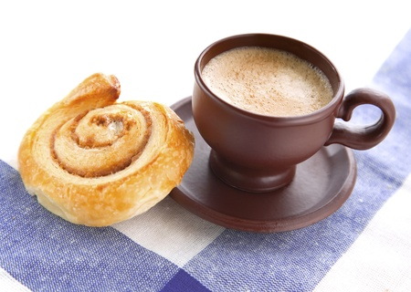 Cup of cofee with cinnamon Danish bun  on textile  background