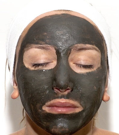 Deep sea mud mask treatment on the woman face photo
