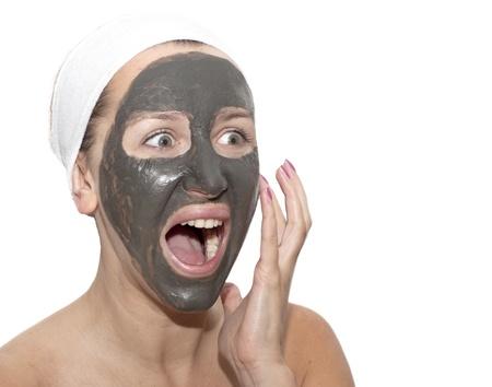 Deep sea mud mask treatment on screaming woman face photo