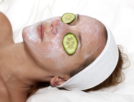 Face treatment. White mask with cucumber on woman face photo