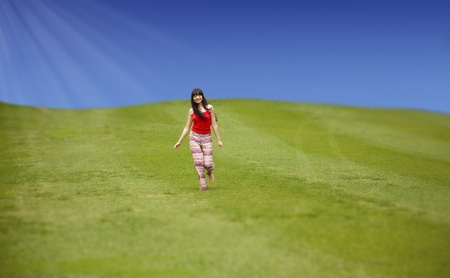 Beautiful young woman running on the green field photo