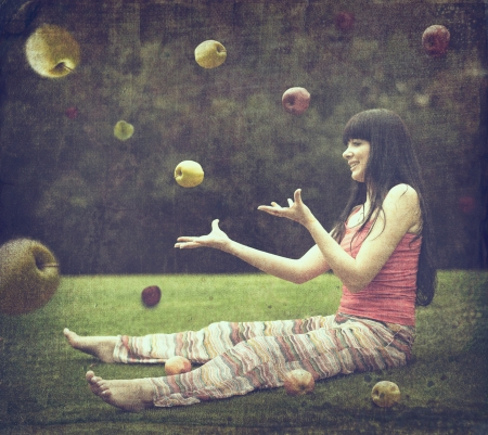 Beautiful young woman on the green meadow with apples. Old style image photo