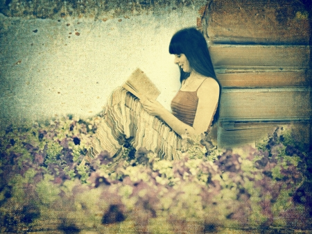 Woman reading book on the meadow. Old image style photo