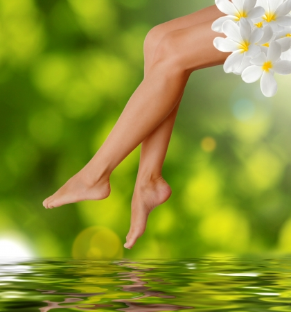 Long woman legs  on green background  Spa concept