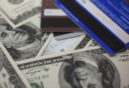 close up image: Dollars with credit card close up image