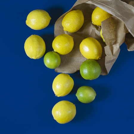 Stil: Pile of lemons in paper shopping bag on blue background Stock Photo
