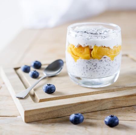 Greek yogurt with mango on the wooden table