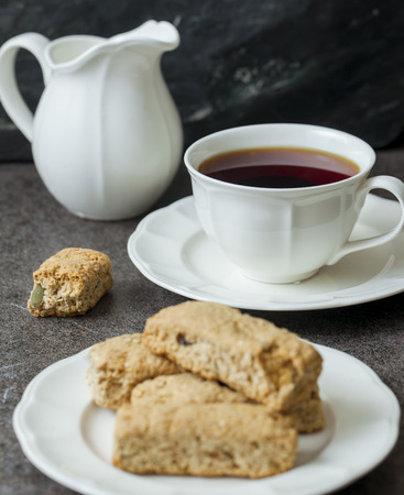 tea table: Cup of tea and saucer with biscuits on the table Stock Photo