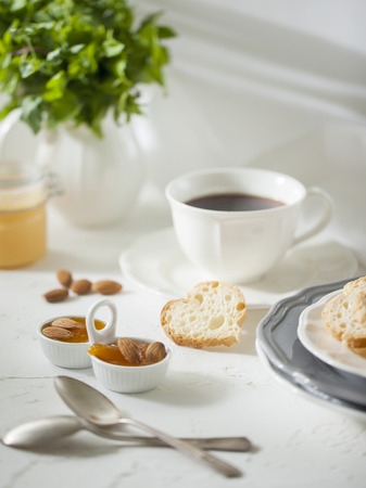 Cup of tea with biscuits and apricot jam on the white table