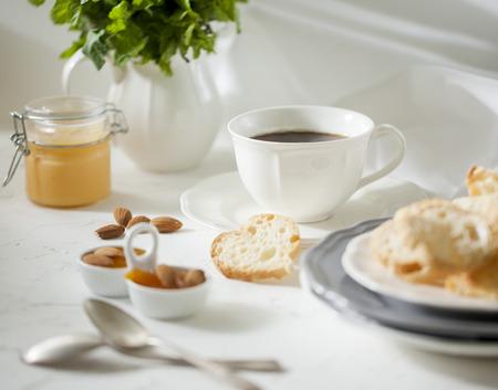 galletas: Taza de té con galletas y mermelada de albaricoque en la mesa blanca