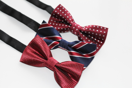 On a white background there are three bow ties for a man. All ties in red and dark colors. This photo is suitable for congratulating men in honor of the day of all men. For mens day.