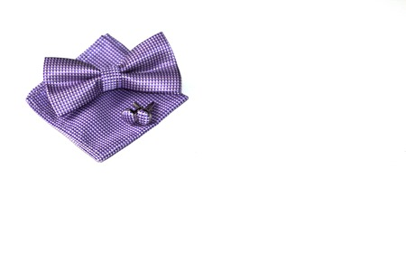 Set for a stylish man: cufflinks, a pocket handkerchief and a bow tie. Everything is located on a white background.