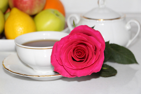 Useful morning breakfast for your sweetheart. Rose, tea and fresh fruits on a white background. Archivio Fotografico