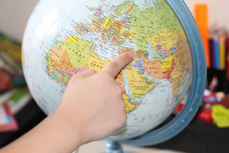 El niño está estudiando geografía. Señalar con el dedo al mundo. Mano de los niños en el fondo de la tarjeta.