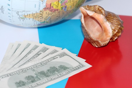 Seashell on dollars background  Nearby is a globe  How to calculate
