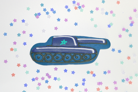 Gingerbread in the form of a tank for the man he loved. Sweet tank for the holiday. Around the tank laid out multi-colored stars. 免版税图像
