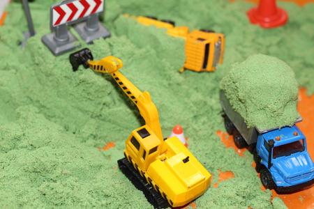 Home sandbox for creativity. Child development at home. In the sandbox green sand, yellow excavator, dump truck. Foto de archivo - 118638923