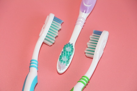 Three toothbrushes on a pink background. Oral hygiene. Brush your teeth with a toothbrush.