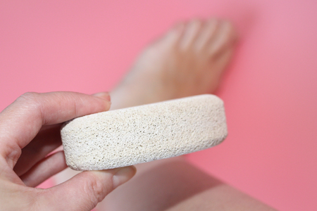 Pumice stone for foot care. In the photo a woman hand holds a pumice near the heel of her foot. Removal of rough skin on the heels of the feet with the help of pumice. Pink background.