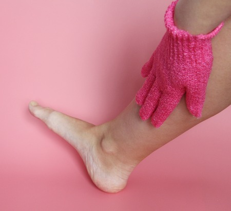 On the female hand wearing a pink glove to wash the body. A woman washes her feet. Shower glove. Pink background. Фото со стока