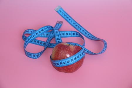 Blue tape for measuring the body around an apple. Apple on a pink background. The concept of losing weight, diet.