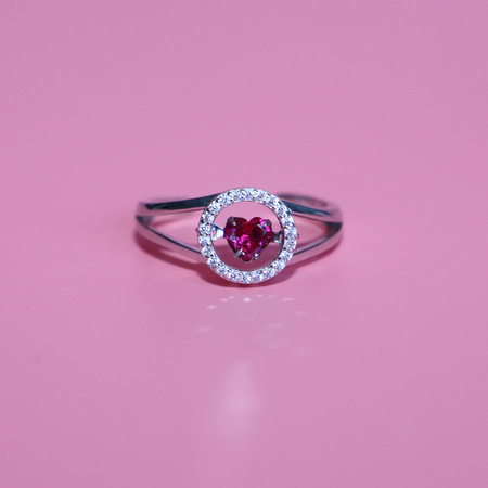 Scarlet heart in a circle. On a pink background. Jewel. Ring with a heart. Declaration of love. Present.