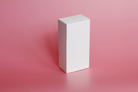 White box stands on a pink background. Vertical white box. Pink background. Box without labels. There are no labels on the package.