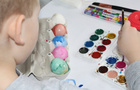 A child paints eggs with a brush. Paint the eggs for Easter. Marble colored eggs. Pastel shades. Easter eggs. Фото со стока