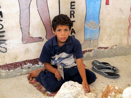 Egypt, Luxor - 07.26.2010: Poor Egyptian boy makes a stone workpiece. The life of modern Egypt. Children of Egypt. A working boy.