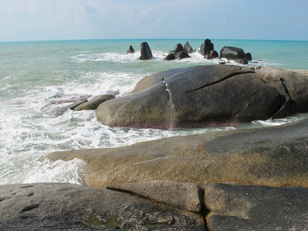 Huge stones on the beach. Boulders on the coast. On the sand are big stones.