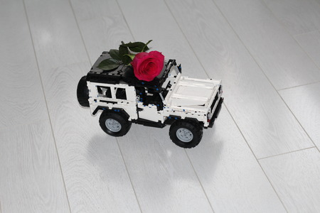 The toy car SUV carries a real red rose. The car is made of designer, it is black and white. Flower delivery.