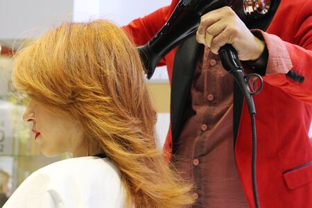 The stylist makes a professional haircut for a young girl. The girl has red hair. Hairdresser blow-dry hair.
