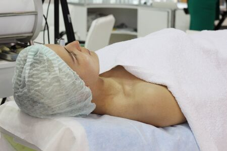 A young woman is lying on the cosmetic bed in the beauty salon. A woman is ready for rejuvenating facial treatments. Peeling face in the beauty parlor. Banque d'images - 133376750